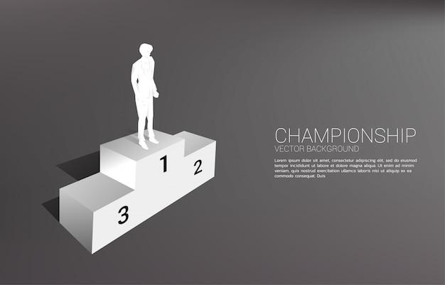 첫 번째 장소 연단에 서 사업가의 실루엣입니다. 승자와 성공의 사업 개념