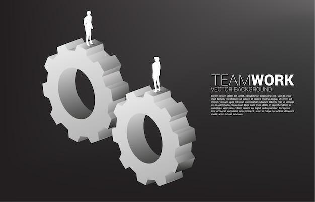一緒に働くためにギアの上に立っているビジネスマンのシルエット。ビジネスチームワークの概念。