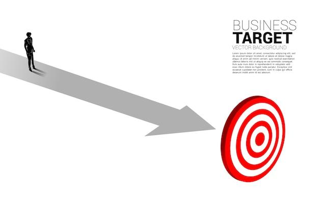 센터 다트 판에 경로에 서있는 사업가의 실루엣. 목표에 대한 경로의 비즈니스 개념과 목표에 직접.