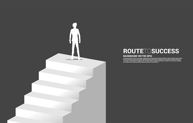 階段に立っているビジネスマンのシルエット。