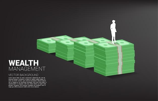 지폐의 스택과 함께 성장 그래프 위에 서있는 사업가의 실루엣. 성공 투자 및 비즈니스 성장의 개념