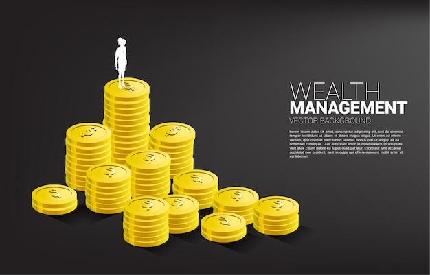 동전 더미 위에 서있는 사업가의 실루엣. 성공 투자 및 비즈니스 성장의 개념