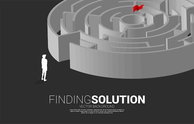 원형 미로 게임으로 서 있는 사업가의 실루엣입니다. 문제 해결 및 아이디어 찾기를 위한 비즈니스 개념입니다.