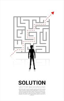 미로에서 나갈 계획으로 서 있는 사업가의 실루엣. 문제 해결 및 솔루션 전략을 위한 비즈니스 개념