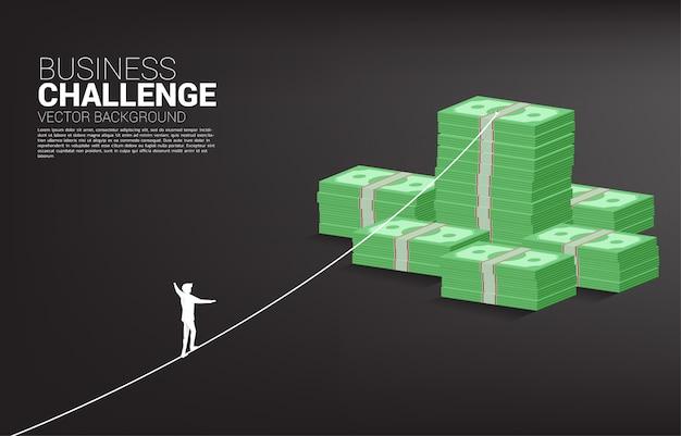 돈 지폐 스택에 밧줄 도보 방법에 걷는 사업가의 실루엣. 사업 위험 및 경력 경로 개념