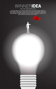 전구에 서있는 붉은 깃발으로 사업가의 실루엣. 창의적인 아이디어와 솔루션의 비즈니스 개념입니다.