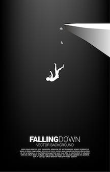 절벽에서 아래로 떨어지는 사업가의 실루엣입니다. 실패 및 우발적 비즈니스에 대한 개념