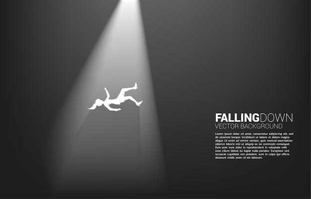빛에서 아래로 떨어지는 사업가의 실루엣입니다. 실패 및 우발적 비즈니스에 대한 개념