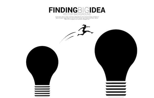 実業家のシルエットは、スプリングボードで電球にジャンプします。創造的なアイデアとソリューションのビジネスコンセプト。
