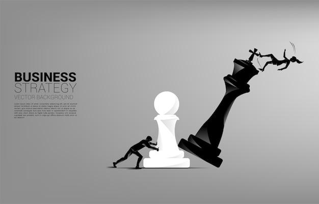 Силуэт бизнес-леди толкает пешку шахматную фигуру, чтобы поставить мат королю с падающим бизнесменом.