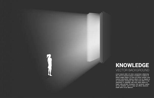 開いた本から光の中で立っている実業家のシルエット。本の知識の概念