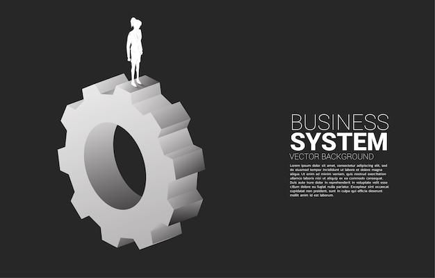 큰 장비에 서있는 사업가의 실루엣입니다. 경영 및 통제의 기치