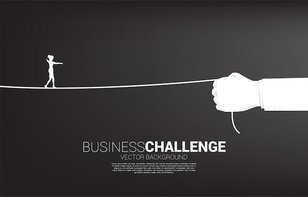 実業家のシルエットは、実業家の手でロープを歩く。ビジネスの課題とキャリアパスの概念。