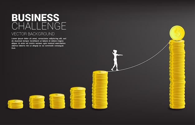 ゴールデンコインスタックグラフにロープの散歩道を歩く実業家のシルエット。ビジネスリスクと挑戦の概念。