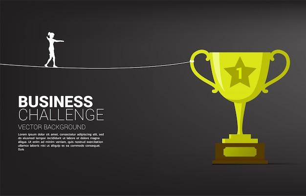 ゴールデントロフィーへのロープの散歩道を歩く実業家のシルエット。ビジネスリスクと挑戦の概念。