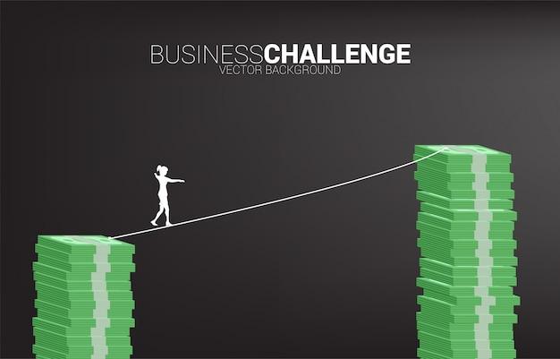 높은 지폐 스택에 밧줄 도보 방법에 걷는 사업가의 실루엣. 사업 위험 및 경력 경로 개념