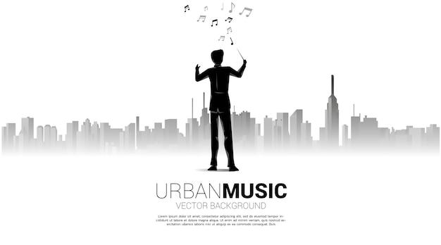 Силуэт дирижера, стоя на фоне города. концепция города музыки.