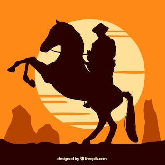 Silhouette of cowboy riding at sunset
