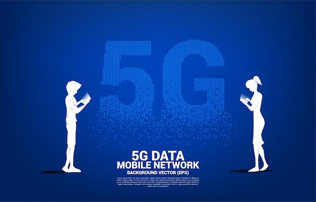 男と女のシルエットは、5 gの未来的なピクセル変換の背景を持つ携帯電話を使用します。自宅から離れた場所で仕事をするためのコンセプトとテクノロジー。