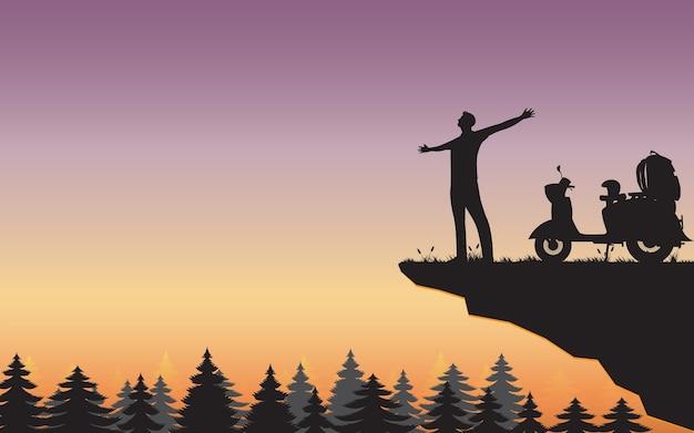 山の崖の上でリラックスして立っている男のシルエット