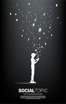 男のシルエットは、携帯電話と飛んでハッシュタグを使用します。社会的なトピックとニュースの背景概念。