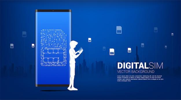 男のシルエットは、画面上のデジタルsimで携帯電話を使用します。モバイル技術とネットワークのコンセプトです。