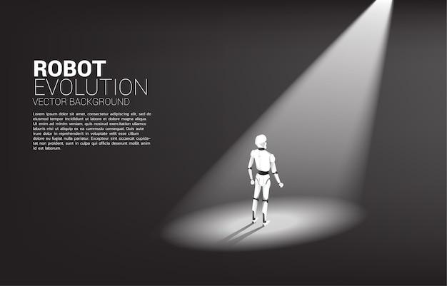 스포트 라이트에 서있는 로봇의 실루엣입니다. 인공 지능 및 기계 학습 작업자 기술의 개념
