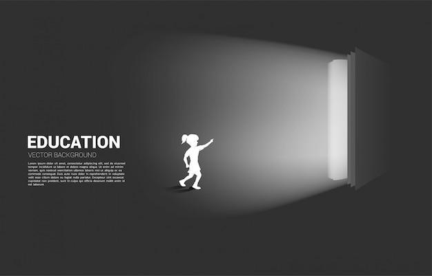 実行中の女の子のシルエットは、開いた本からの光を指します。教育ソリューションの概念。知識の世界。