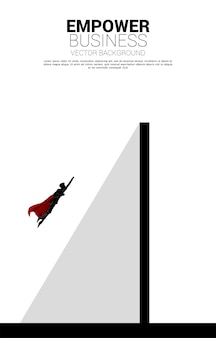 슈퍼히어로의 실루엣이 벽 너머로 날아갑니다. 비즈니스 도전 및 권한 부여의 개념입니다.