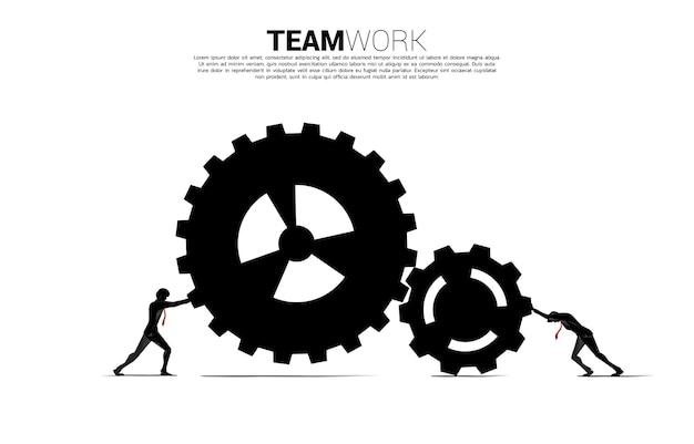 仕事にギアを押す2人のビジネスマンのシルエット。ビジネスチームワークの概念。