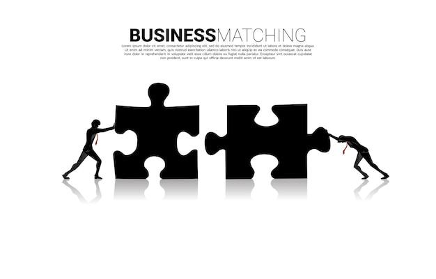 2つのジグソーピースパズルを押す2人のビジネスマンのシルエット。ビジネスチームワークの概念。