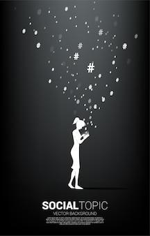 女性のシルエットは、携帯電話と飛んでハッシュタグを使用します。社会的なトピックとニュースの背景概念。