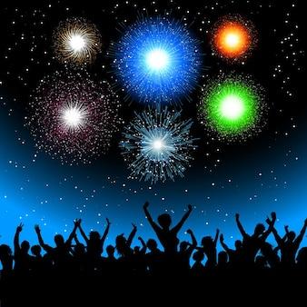 Silhouette di una folla di partito contro un cielo pieno di fuochi d'artificio che esplodono