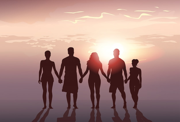Silhouette people group stand holding hands man and woman full length over sunset background