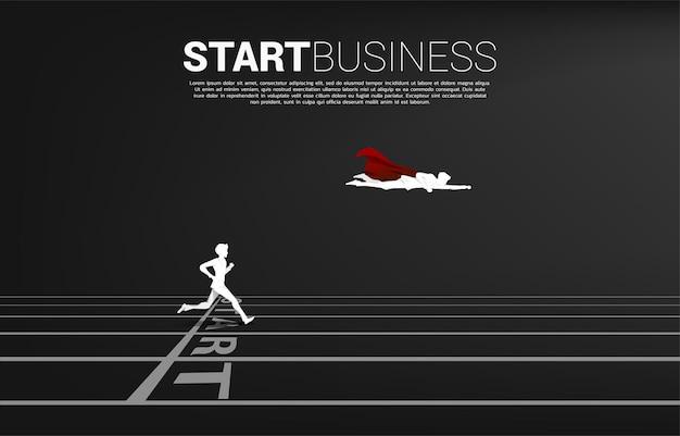 실루엣 슈퍼 히어로는 출발선에서 사업가 위로 날아갑니다. 경력과 사업을 시작할 준비가 된 사람들의 개념