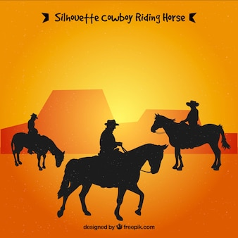 Silhouette of three cowboys riding
