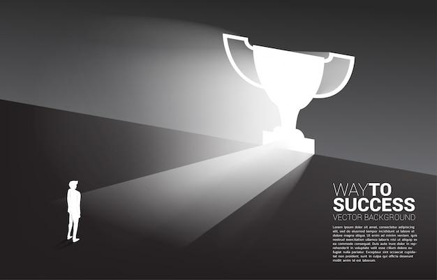 Silhouette бизнесмен стоя в свете от трофея формы двери выхода. деловой маршрут к победителю и чемпиону