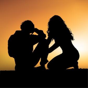 日没時のシルエットのカップル