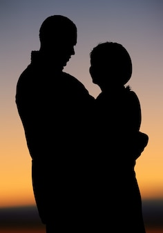 Silhouetted couple at sunset Premium Vector