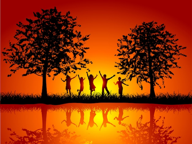 Silhouettes of children playing outside alongside a river