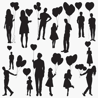 Silhouettes holding heart shaped balloons