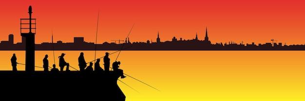 Силуэты рыбаков с удочками на пирсе с маяком и длинным горизонтом города на фоне заката. много людей с длинными удочками с копировальным пространством.