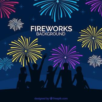 Silhouettes of people enjoying fireworks background