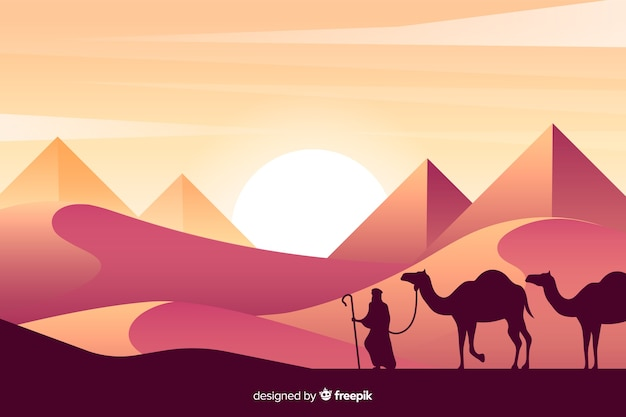 Silhouettes of person and camels in desert