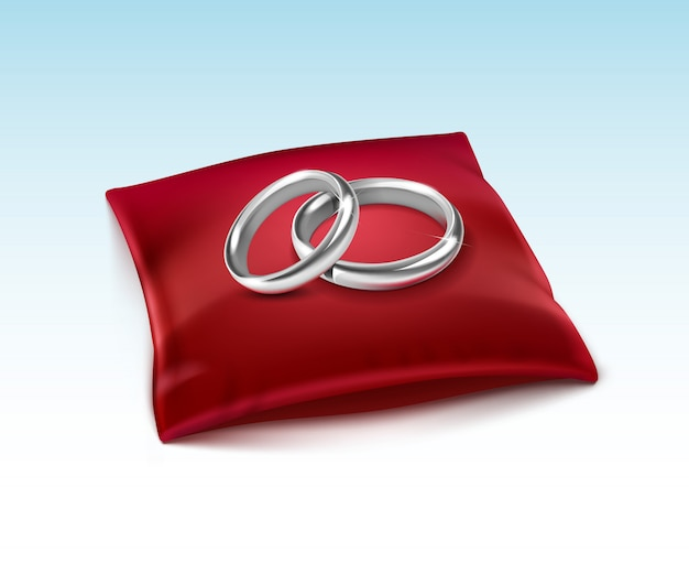 白で隔離赤いサテンの枕の上の銀の結婚指輪