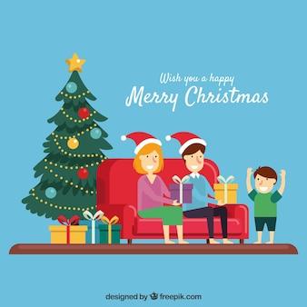 プレゼント付きのクリスマスツリーの横のソファに座って