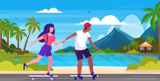 바닷가 스케이트 보드 개념에 트릭을 수행하는 스케이터 커플