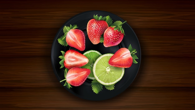 Sliced lime and strawberries on a dark plate and wooden table.