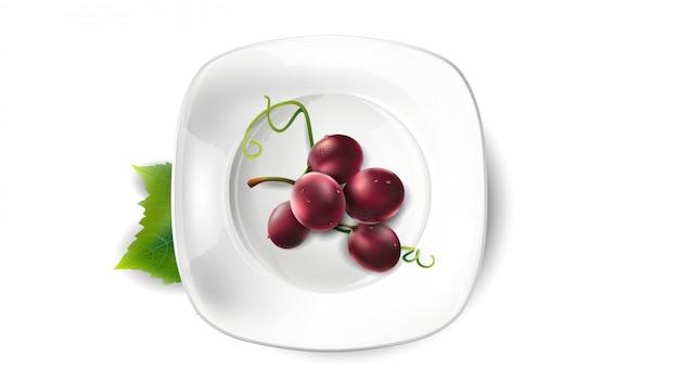 白い皿に赤いブドウの小さな束。