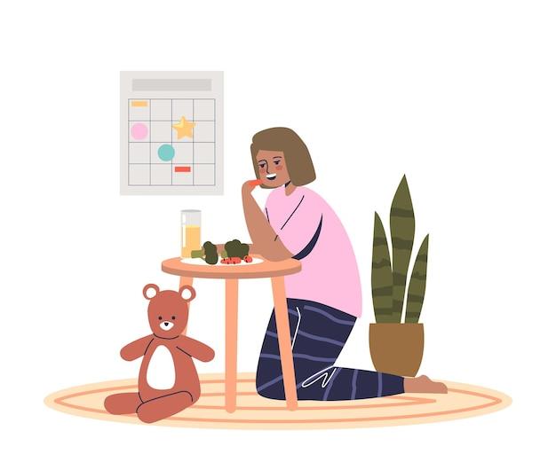 朝食に野菜を食べる小さな女の子。小さな就学前の子供はビタミンでいっぱいの健康的な食事を楽しんでいます